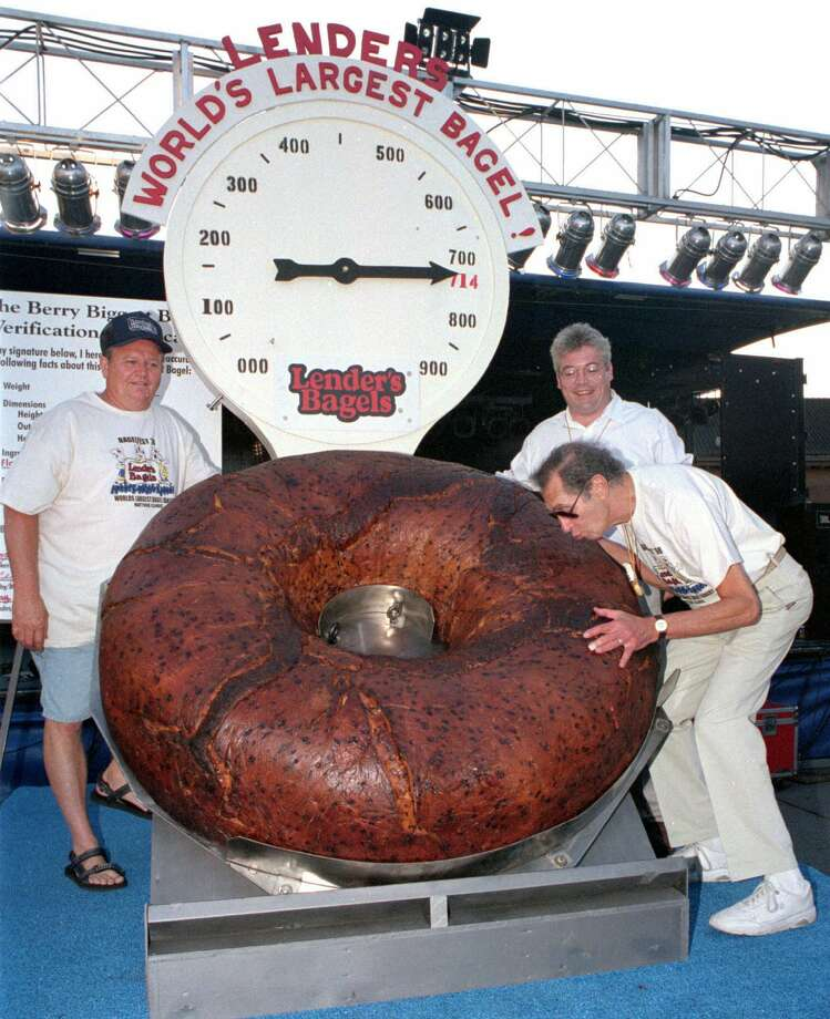 Murray Lender kisses the world's largest bagel while baker Larry Wilkerson (left) and Lender's Bagel Bakery manager Jim Cudahy watch after the weight of the bagel was revealed to be 714 pounds during Bagelfest in Mattoon, Ill., on July 24, 1998. Photo: Doug Lawhead, AP Photo / Journal Gazette / AP1998