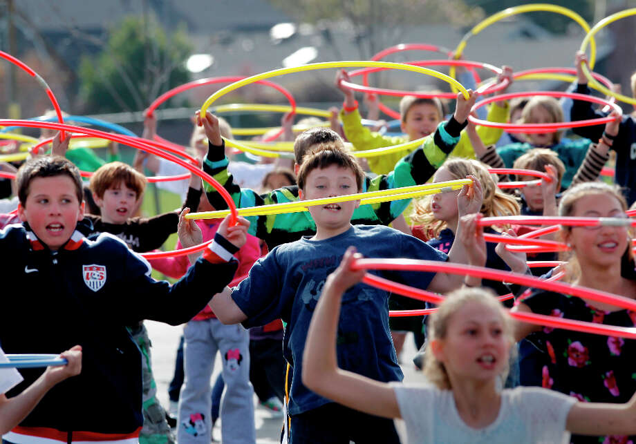 The hula hoop workouts included aerobic exercise with the hoops and little hip action. Del Rey Elementary School in Orinda, Calif. assembled about 400 of their students on the playground Monday March 25, 2013 to try to break the Hula Hoop workout record for the Guinness World Records. Photo: Brant Ward, The Chronicle / ONLINE_YES