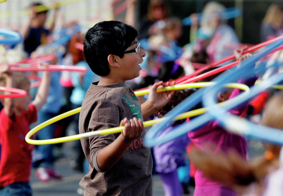 A Del Rey student works out with his hula hoop. Del Rey Elementary School in Orinda, Calif. assembled about 400 of their students on the playground Monday March 25, 2013 to try to break the Hula Hoop workout record for the Guinness World Records. Photo: Brant Ward, The Chronicle / ONLINE_YES