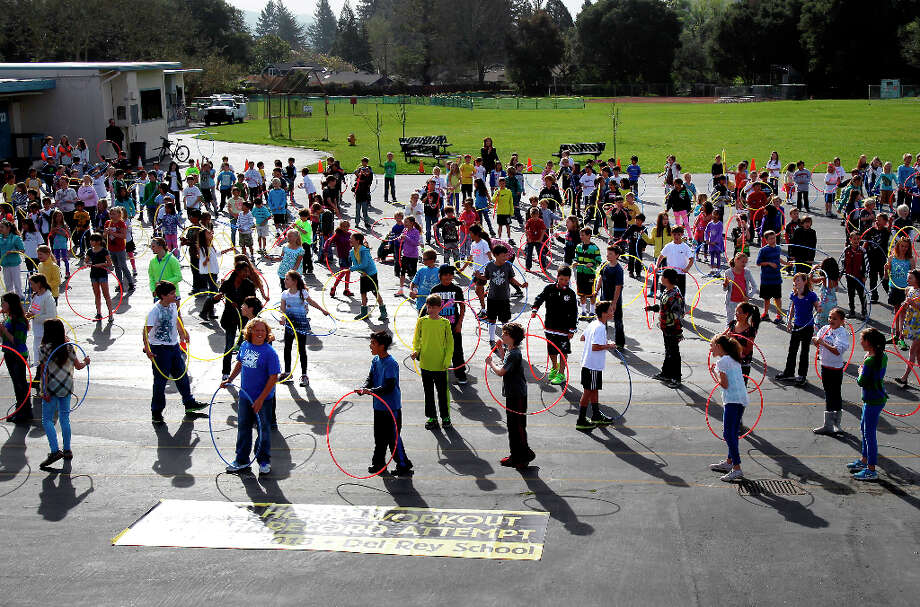 The students assembled on the playground and paused to celebrate a birthday after finishing their workout. Del Rey Elementary School in Orinda, Calif. assembled about 400 of their students on the playground Monday March 25, 2013 to try to break the Hula Hoop workout record for the Guinness World Records. Photo: Brant Ward, The Chronicle / ONLINE_YES
