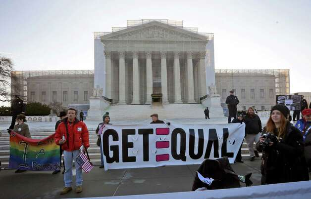 Demonstrators stand outside the Supreme Court in Washington, Tuesday, March 26, 2013, where the court will hear arguments on California's voter approved ban on same-sex marriage, Proposition 8. Photo: Pablo Martinez Monsivais