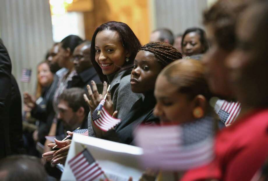 NEW YORK, NY - MARCH 22:  Immigrants celebrate after becoming American citizens at a naturalization ceremony at Federal Hall on March 22, 2013 in New York City. Seventy-four immigrants from 39 different countries took part in the event held in the historic building where George Washington took the oath of office as the first President of the United States. The event was held by U.S. Immigrant and Citizenship Services (USCIS). Photo: John Moore, Getty Images / 2013 Getty Images