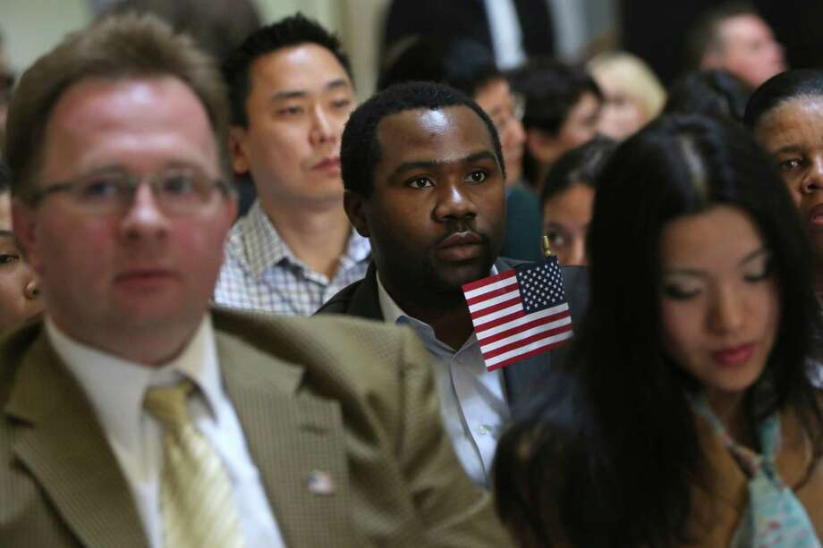 Zoltan Sznorfi, left, originally from Hungary, Benjamin Njoku, center, originally from Nigeria, and Keyan Chen, right, originally from China wait for the naturalization ceremony at historic Federal Hall to start, Friday, March 22, 2013 in New York. The 75 citizenship candidates currently live in Manhattan or the Bronx and originate from 40 countries including Argentina, Australia, Brazil, Cameroon, Canada, People's Republic of China, Colombia, Croatia, Egypt, El Salvador, France, Georgia, Ghana, Guatemala, Guinea, Haiti, Hungary, Japan, Latvia, Mexico, the Netherlands, Nigeria, Senegal, South Korea,Turkey, Ukraine, United Kingdom, Venezuela and Vietnam. Photo: Mary Altaffer, AP / AP