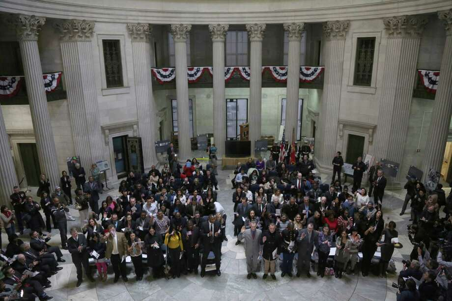 Participants take the Oath of Allegiance during a naturalization ceremony at historic Federal Hall, Friday, March 22, 2013 in New York. The 75 citizenship candidates currently live in Manhattan or the Bronx and originate from 40 countries including Argentina, Australia, Brazil, Cameroon, Canada, People's Republic of China, Colombia, Croatia, Egypt, El Salvador, France, Georgia, Ghana, Guatemala, Guinea, Haiti, Hungary, Japan, Latvia, Mexico, the Netherlands, Nigeria, Senegal, South Korea,Turkey, Ukraine, United Kingdom, Venezuela and Vietnam. Photo: Mary Altaffer, AP / AP