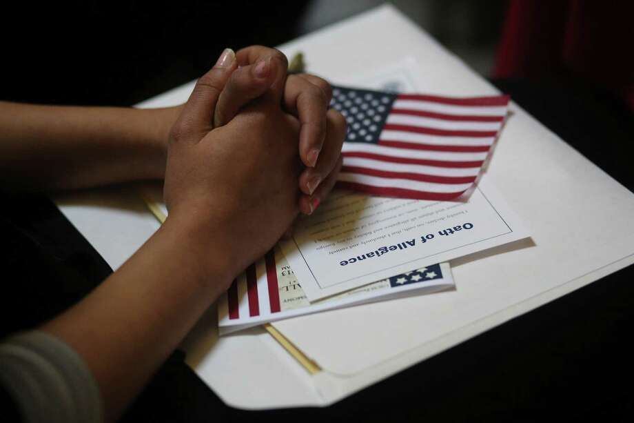 A participant fold her hands of a copy of the Oath of Allegiance while listening to speeches during a naturalization ceremony at historic Federal Hall, Friday, March 22, 2013 in New York. The 75 citizenship candidates currently live in Manhattan or the Bronx and originate from 40 countries including Argentina, Australia, Brazil, Cameroon, Canada, People's Republic of China, Colombia, Croatia, Egypt, El Salvador, France, Georgia, Ghana, Guatemala, Guinea, Haiti, Hungary, Japan, Latvia, Mexico, the Netherlands, Nigeria, Senegal, South Korea,Turkey, Ukraine, United Kingdom, Venezuela and Vietnam. Photo: Mary Altaffer, AP / AP