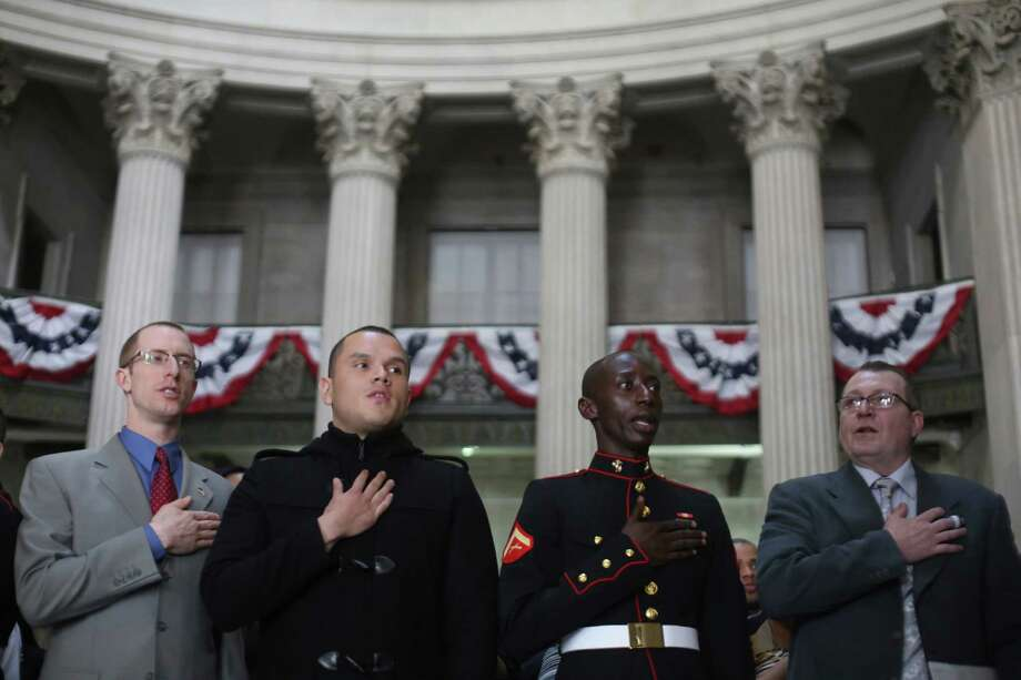 Army reserve chaplain Eliezer Jeffrey David Bercoson, left, originally from Canada, Lance Corporal Alex Ricardo Arteaga Haro, second from left, originally from Ecuador, Lance Corporal Torffic Hassan, second from right, originally from Ghana and Jose Campo, originally from Venezuela, pledge their allegiance to the American flag during a naturalization ceremony at historic Federal Hall, Friday, March 22, 2013 in New York. The 75 citizenship candidates currently live in Manhattan or the Bronx and originate from 40 countries including Argentina, Australia, Brazil, Cameroon, Canada, People's Republic of China, Colombia, Croatia, Egypt, El Salvador, France, Georgia, Ghana, Guatemala, Guinea, Haiti, Hungary, Japan, Latvia, Mexico, the Netherlands, Nigeria, Senegal, South Korea,Turkey, Ukraine, United Kingdom, Venezuela and Vietnam. Photo: Mary Altaffer, AP / AP