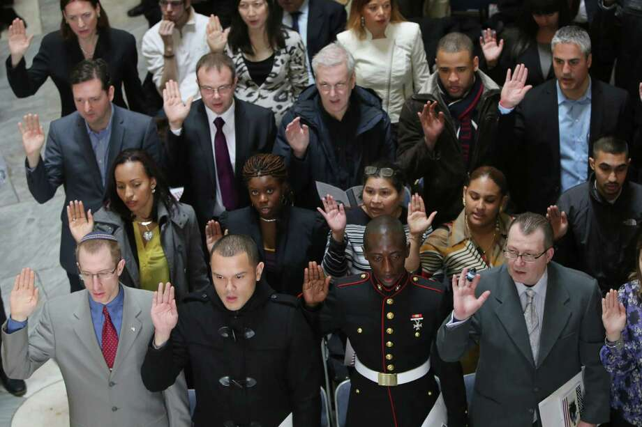 Army reserve chaplain Eliezer Jeffrey David Bercoson, first row left, originally from Canada, Lance Corporal Alex Ricardo Arteaga Haro, second from left, originally from Ecuador, Lance Corporal Torffic Hassan, second from right, originally from Ghana and Jose Campo, originally from Venezuela, join others as they take the Oath of Allegiance during a naturalization ceremony at historic Federal Hall, Friday, March 22, 2013 in New York. The 75 citizenship candidates currently live in Manhattan or the Bronx and originate from 40 countries including Argentina, Australia, Brazil, Cameroon, Canada, People's Republic of China, Colombia, Croatia, Egypt, El Salvador, France, Georgia, Ghana, Guatemala, Guinea, Haiti, Hungary, Japan, Latvia, Mexico, the Netherlands, Nigeria, Senegal, South Korea,Turkey, Ukraine, United Kingdom, Venezuela and Vietnam. Photo: Mary Altaffer, AP / AP