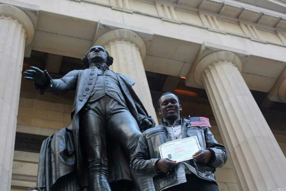 Babacar Ndiaye, originally from Senegal, poses for a photo outside Federal Hall after becoming an American citizen during a naturalization ceremony, Friday, March 22, 2013 in New York. The 75 citizenship candidates currently live in Manhattan or the Bronx and originate from 40 countries including Argentina, Australia, Brazil, Cameroon, Canada, People's Republic of China, Colombia, Croatia, Egypt, El Salvador, France, Georgia, Ghana, Guatemala, Guinea, Haiti, Hungary, Japan, Latvia, Mexico, the Netherlands, Nigeria, Senegal, South Korea,Turkey, Ukraine, United Kingdom, Venezuela and Vietnam. Photo: Mary Altaffer, AP / AP