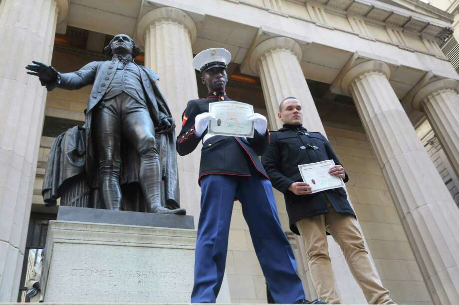 Lance Corporal Torffic Hassan, left, originally from Ghana and Lance Corporal Alex Ricardo Arteaga Haro, originally from Ecuador, pose for a photo outside Federal Hall after becoming an American citizen during a naturalization ceremony, Friday, March 22, 2013 in New York. The 75 citizenship candidates currently live in Manhattan or the Bronx and originate from 40 countries including Argentina, Australia, Brazil, Cameroon, Canada, People's Republic of China, Colombia, Croatia, Egypt, El Salvador, France, Georgia, Ghana, Guatemala, Guinea, Haiti, Hungary, Japan, Latvia, Mexico, the Netherlands, Nigeria, Senegal, South Korea,Turkey, Ukraine, United Kingdom, Venezuela and Vietnam. Photo: Mary Altaffer, AP / AP