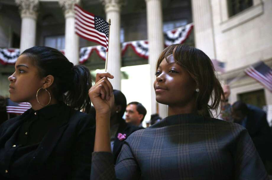 NEW YORK, NY - MARCH 22:  Immigrants wave U.S. flags after becoming American citizens at a naturalization ceremony at Federal Hall on March 22, 2013 in New York City. Seventy-four immigrants from 39 different countries took part in the event held in the historic building where George Washington took the oath of office as the first President of the United States. The event was held by U.S. Immigrant and Citizenship Services (USCIS). Photo: John Moore, Getty Images / 2013 Getty Images