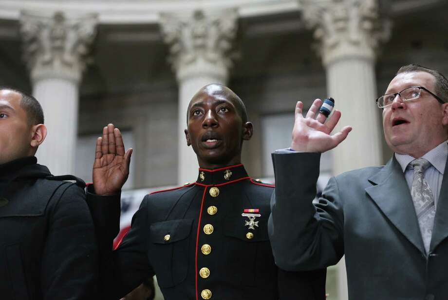 NEW YORK, NY - MARCH 22:  Immigrants, including U.S. Marine Lcpl. Torffic Hassan (C) from Ghana take the oath of allegiance to the United States to become American citizens at Federal Hall on March 22, 2013 in New York City. Seventy-four immigrants from 39 different countries took part in naturalization ceremony held in the historic building where George Washington took the oath of office as the first President of the United States. Photo: John Moore, Getty Images / 2013 Getty Images