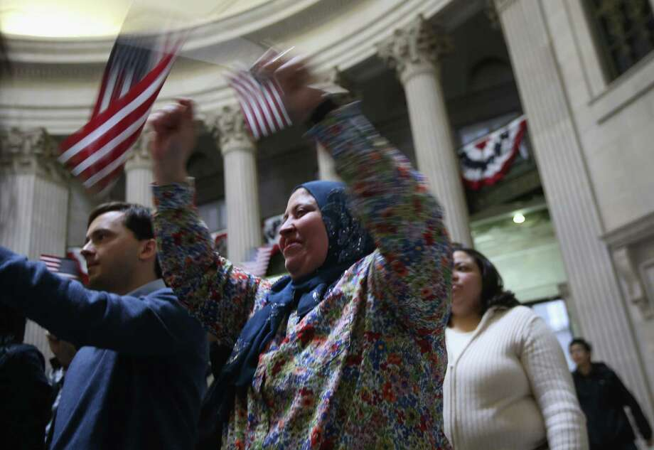 NEW YORK, NY - MARCH 22:  Immigrants celebrate after taking the oath of allegiance to the United States to become American citizens at Federal Hall on March 22, 2013 in New York City. Seventy-four immigrants from 39 different countries took part in naturalization ceremony held in the historic building where George Washington took the oath of office as the first President of the United States. Photo: John Moore, Getty Images / 2013 Getty Images