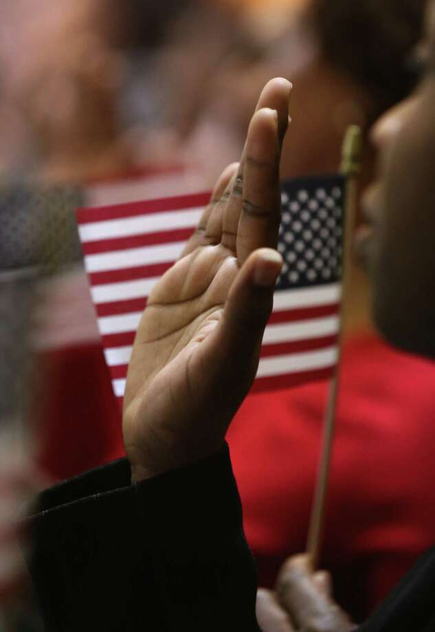 NEW YORK, NY - MARCH 22:  Immigrants raise their hands for the oath of allegiance to the United States to become American citizens at Federal Hall on March 22, 2013 in New York City. Seventy-four immigrants from 39 different countries took part in naturalization ceremony held in the historic building where George Washington took the oath of office as the first President of the United States. Photo: John Moore, Getty Images / 2013 Getty Images