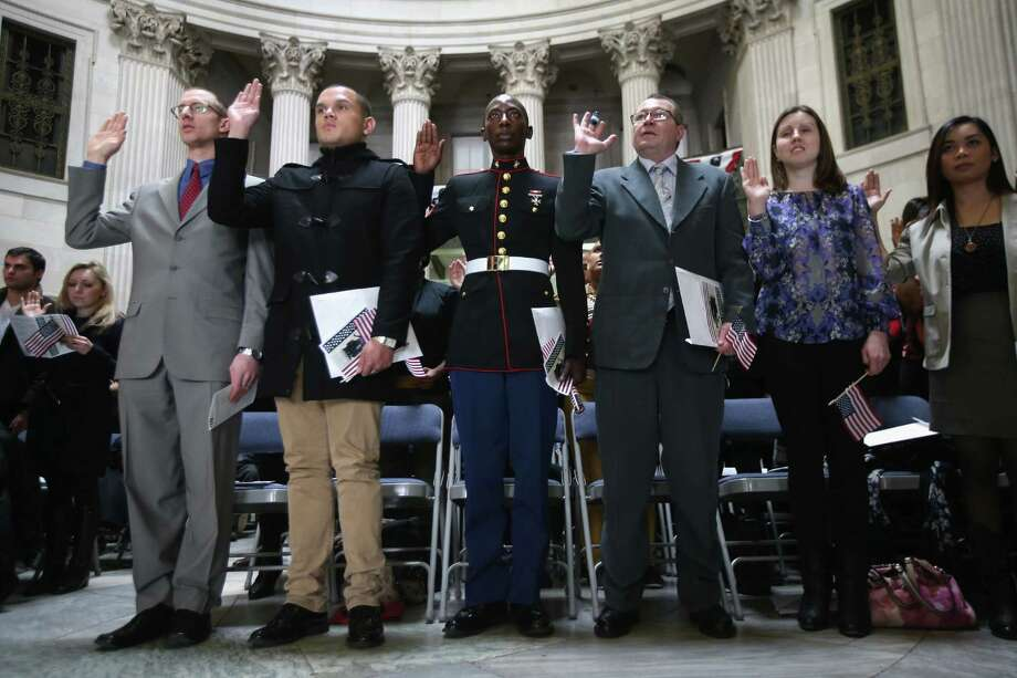 NEW YORK, NY - MARCH 22:  Immigrants, including U.S. Marine Lcpl. Torffic Hassan (3rd L) from Ghana take the oath of allegiance to the United States to become American citizens at Federal Hall on March 22, 2013 in New York City. Seventy-four immigrants from 39 different countries took part in naturalization ceremony held in the historic building where George Washington took the oath of office as the first President of the United States. Photo: John Moore, Getty Images / 2013 Getty Images