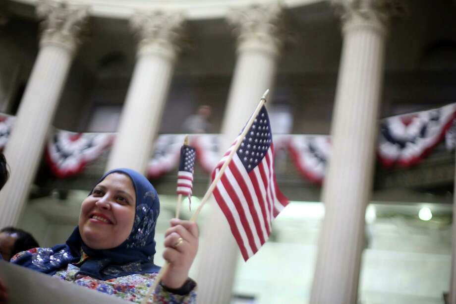 Fatma Atia, who is originally from Egypt and lives in the Bronx borough of New York, waves an American flag during a naturalization ceremony at historic Federal Hall, Friday, March 22, 2013 in New York. The 75 citizenship candidates currently live in Manhattan or the Bronx and originate from 40 countries including Argentina, Australia, Brazil, Cameroon, Canada, People's Republic of China, Colombia, Croatia, Egypt, El Salvador, France, Georgia, Ghana, Guatemala, Guinea, Haiti, Hungary, Japan, Latvia, Mexico, the Netherlands, Nigeria, Senegal, South Korea,Turkey, Ukraine, United Kingdom, Venezuela and Vietnam. Photo: Mary Altaffer, AP / AP