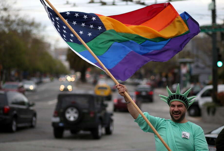 SAN FRANCISCO, CA - MARCH 25:  Same-sex marriage supporter Nikolas Lemos waves a Pride flag during a rally in support of marriage equality on March 25, 2013 in San Francisco, California. Supporters of same-sex marriage held a rally and are set to march through San Francisco a day before the U.S. Supreme Court will hear arguments on California's Proposition 8, the controversial ballot initiative that defines marriage as between a man and a woman. Photo: Justin Sullivan, Getty Images / 2013 Getty Images