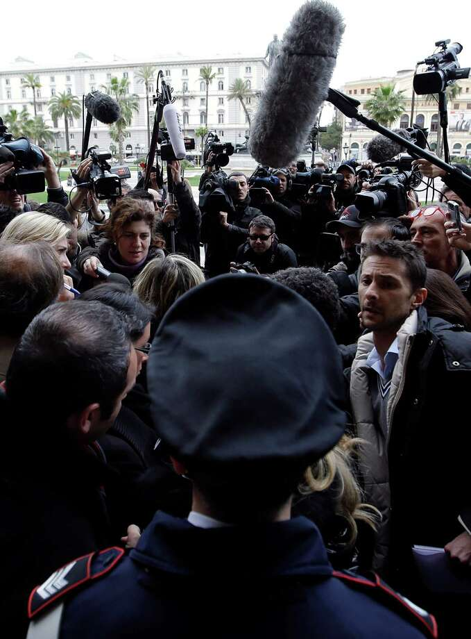 Journalists listen to Giulia Bongiorno, lawyer of Amanda Knox's ex-boyfriend, Raffaele Sollecito, hidden back to camera, outside the main gate of the Cassation court building as journalists listen to Giulia Bongiorno, lawyer of Amanda Knox's ex-boyfriend, Raffaele Sollecito, in Rome, Tuesday. Photo: Gregorio Borgia, AP