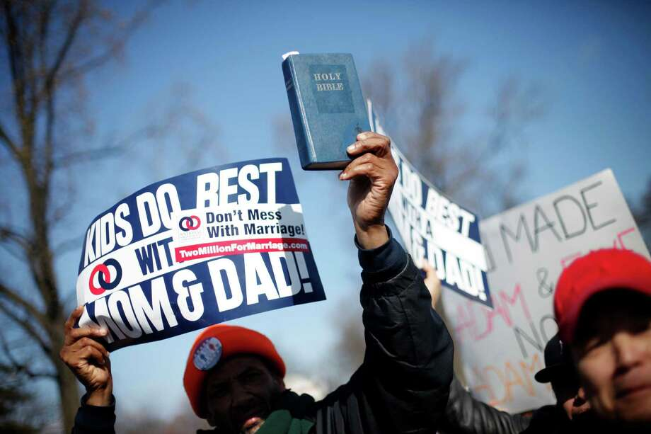 A demonstrator holds a bible while marching outside the Supreme Court in Washington, Tuesday, March 26, 2013, as the court heard arguments on California's voter approved ban on same-sex marriage, Proposition 8. The Supreme Court waded into the fight over same-sex marriage Tuesday, at a time when public opinion is shifting rapidly in favor of permitting gay and lesbian couples to wed, but 40 states don't allow it. Photo: Pablo Martinez Monsivais
