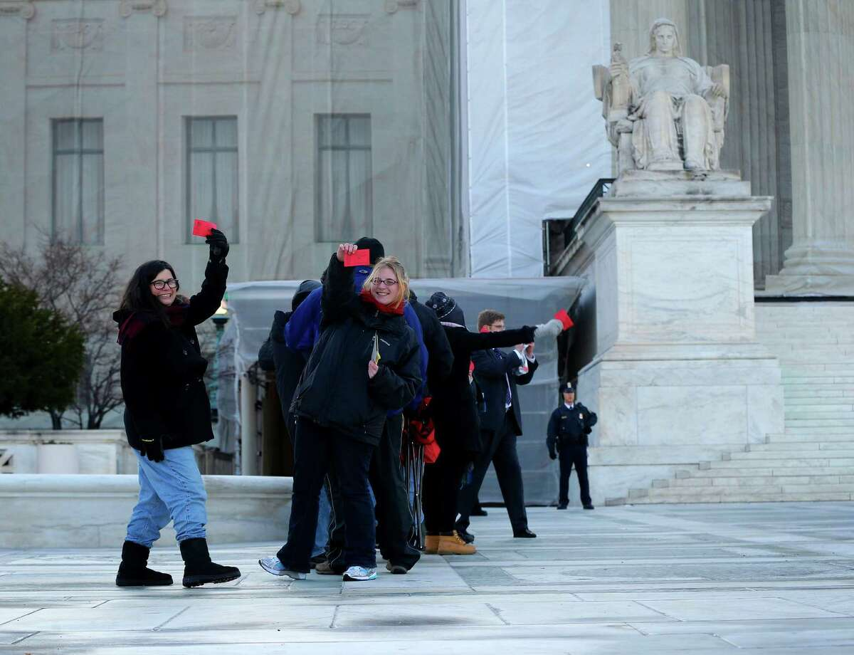People hold up their tickets that had been issued to the general public for entrance Supreme Court in Washington, Tuesday, March 26, 2013, for the court's hearing on California's voter approved ban on same-sex marriage. Some people waited in line _ even through light snow _ since Thursday for the coveted seats for the argument over California's Proposition 8.