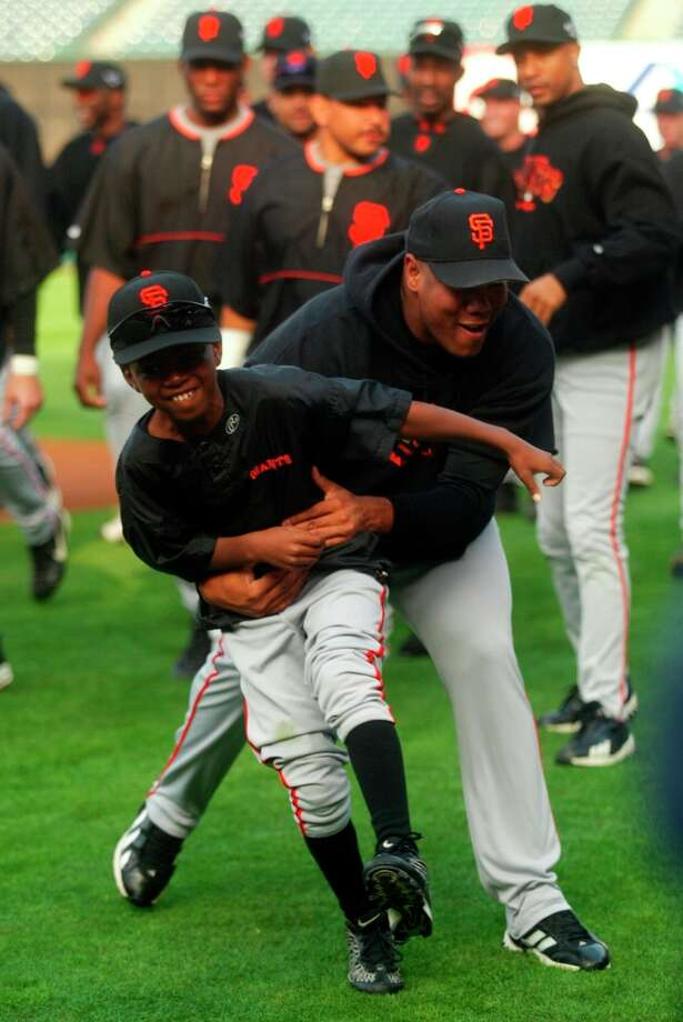 Giants pitcher Livan Hernandez grabs Shawon Dunston Jr., 9, the son of teammate Shawon Dunston, during team practice October 18, 2002.  The San Francisco Giants vs. the Anaheim Angels in the World Series with games one and two being played in Anaheim. Photo: Mike Kepka, SFC / Chronicle