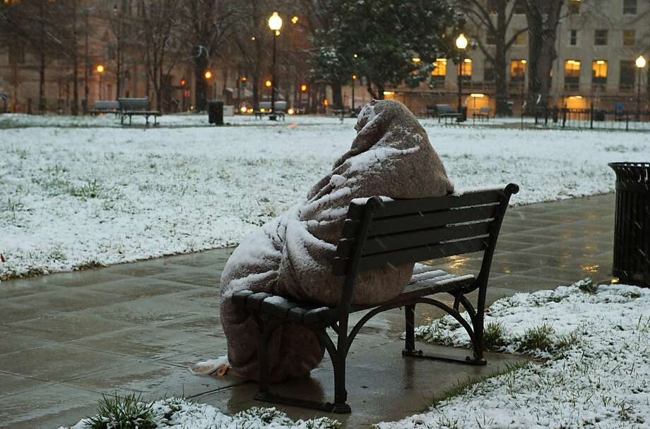 Snow settles on the blanket of a homeless man during a winter storm in the nation's capital. Photo: Karen Bleier, AFP/Getty Images