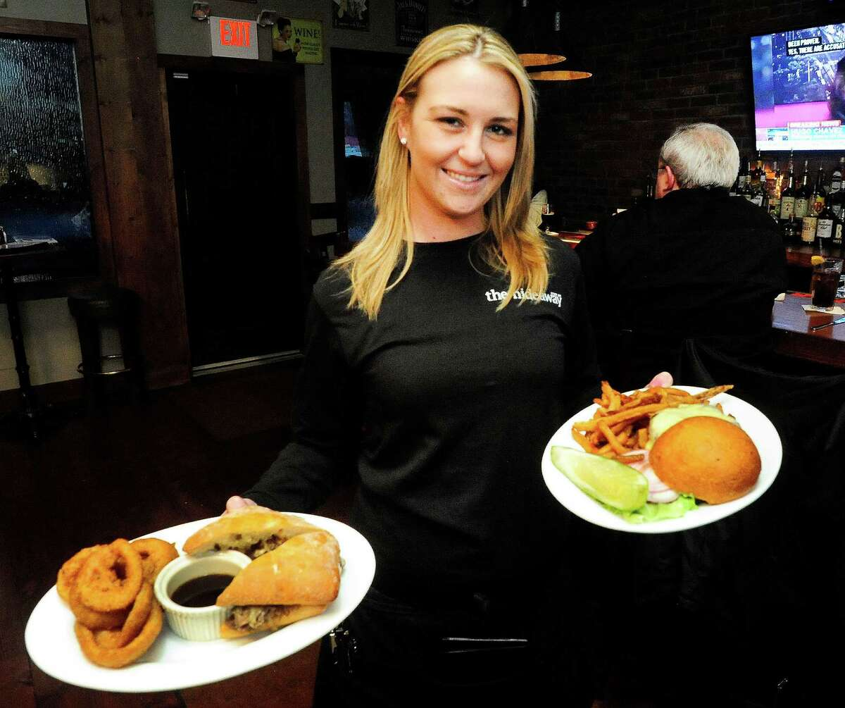 Server Kelly Taylor holds The Balboa, left, and the bacon cheeseburger at The Hideaway Kitchen & Bar, in Ridgefield, Conn. Tuesday, March 5, 2013.
