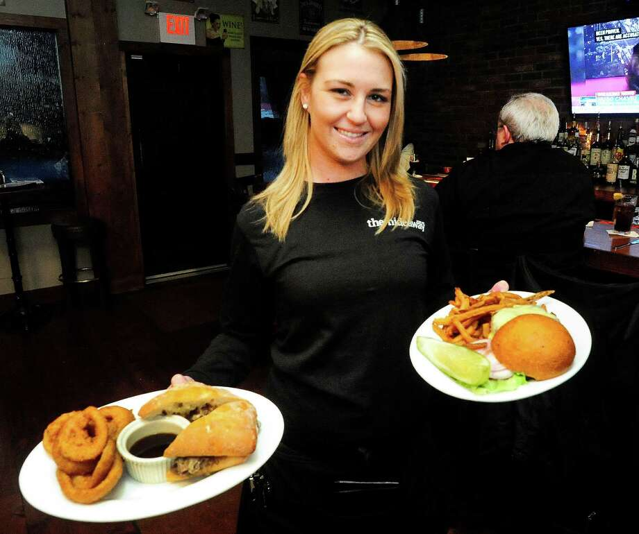 Server Kelly Taylor holds The Balboa, left, and the bacon cheeseburger at The Hideaway Kitchen & Bar, in Ridgefield, Conn. Tuesday, March 5, 2013. Photo: Michael Duffy / The News-Times