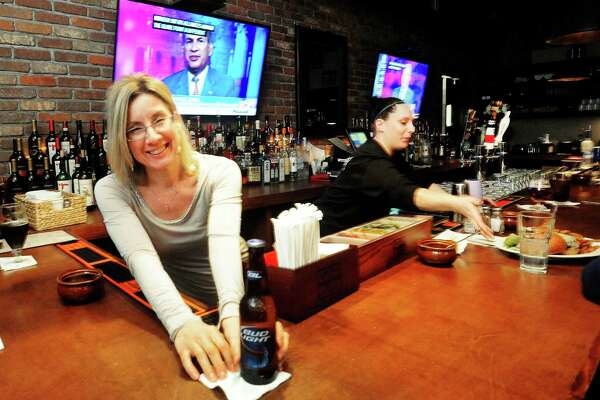 Sherry Bell, left, serves a Bud Light at The Hideaway Kitchen & Bar, in Ridgefield, Conn. Tuesday, March 5, 2013.