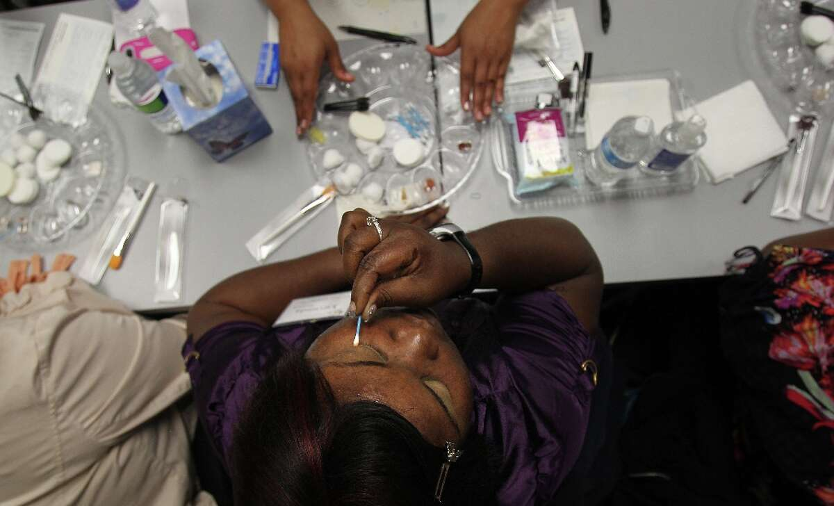 Legally blind makeup consumer Yuvonda Simpson applies eye shadow to her eyelid by feeling and following her eyebrow bone structure on her face.