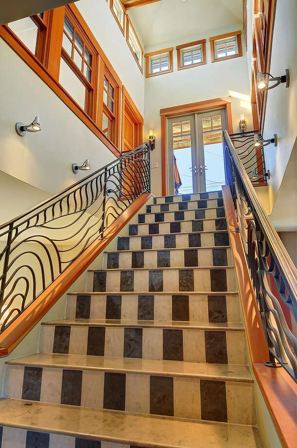Staircase of 2508 57th Ave. S.W. The 2,386-square-foot Mediterranean-style home, built in 2002, has three bedrooms and 3.25 bathrooms -- including a mother-in-law apartment -- limestone floors, iron railings and a balcony on a 1,575-square-foot lot. It's listed for $699,950. Photo: Courtesy Sandra Hines/Windermere Real Estate
