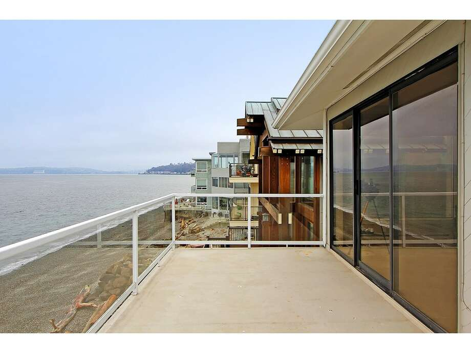 of 3121 Alki Ave. S.W., Unit A. The 1,397-square-foot home, built in 1977, has two bedrooms, 1.75 bathrooms, big windows, a long deck, a sauna, and sound and city views. It's listed for $685,000. Photo: Courtesy Randie Stone/Windermere Real Estate
