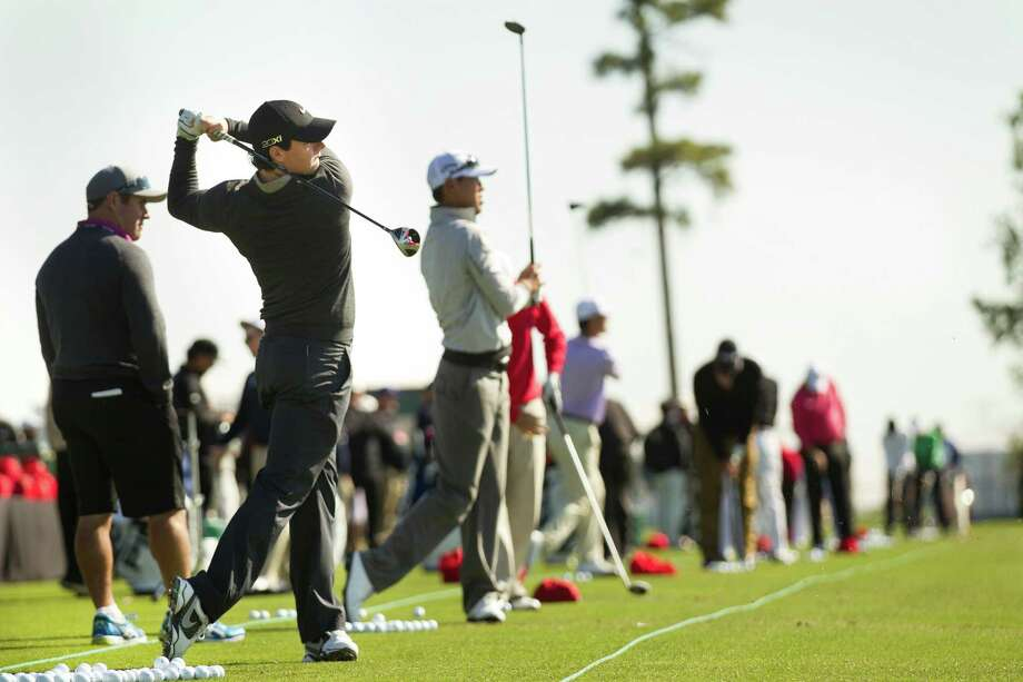Rory McIlroy, left, hits balls on the driving range before a practice round for the Shell Houston Open at the Redstone Tournament Course Tuesday, March 26, 2013, in Humble. Photo: Brett Coomer, Houston Chronicle / © 2013 Houston Chronicle