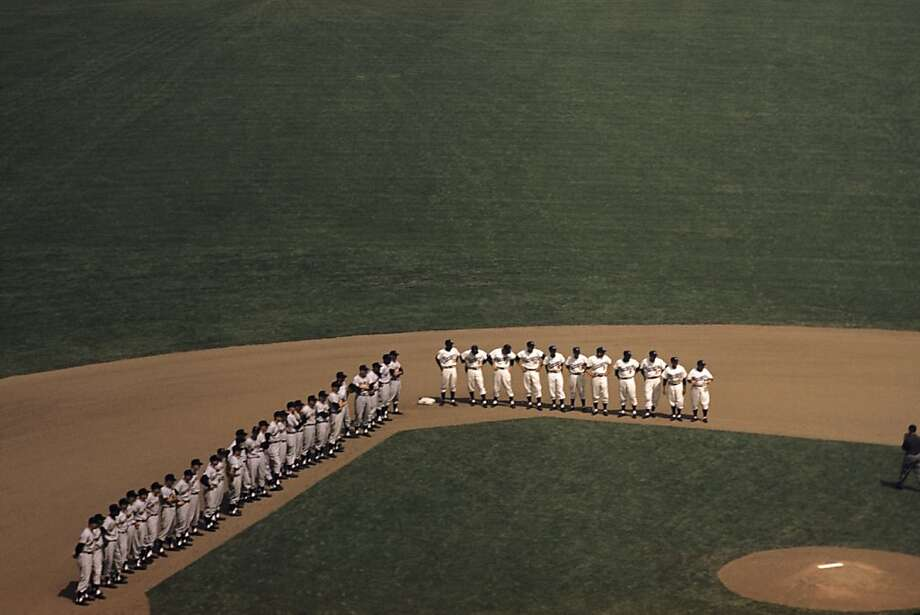 The San Francisco Giants and the Los Angeles Dodgers stand on the basepaths as the Dodgers are introduced to the fans prior to the Opening Day game on April 18, 1958 at the Los Angeles Memorial Coliseum in Los Angeles, California. Photo: Diamond Images, Getty Images