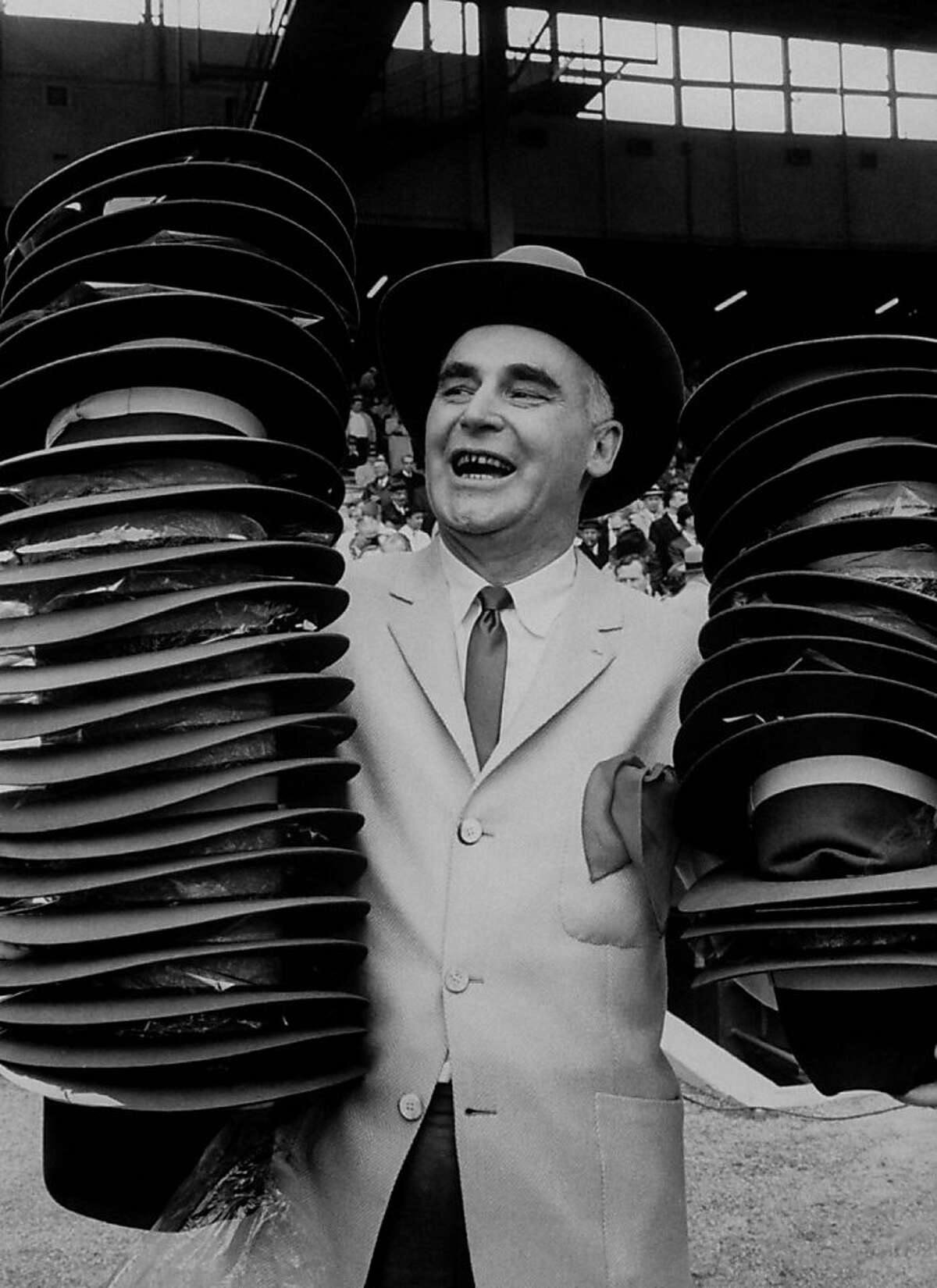 Athletics owner Charlie Finley shows off the green-and-gold 10-gallon hats that were distributed to fans on Opening Day 1963.