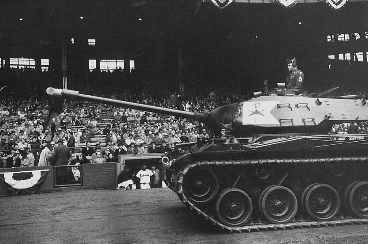 Opening Day 1957: An army tank chugs along the Tiger Stadium foul territory.