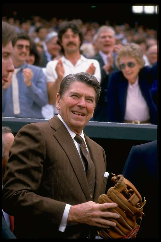 President Ronald Reagan poses with a baseball glove in front of fan-filled stands at the opening game of the Baltimore Orioles' 1986 season. Photo: Diana Walker, Time Life Pictures/Getty Images
