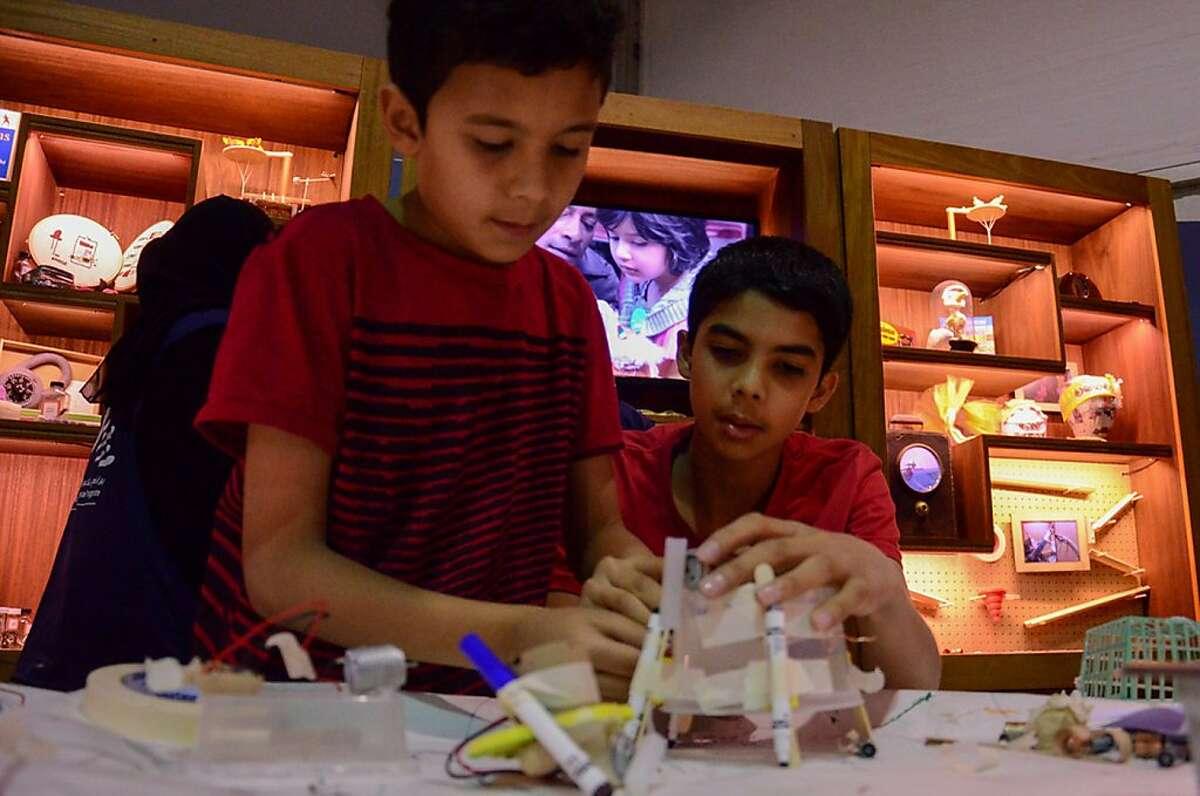 Two boys collaborate in the Tinkering Studio, Saudi Aramco Summer Cultural Program in Al Khobar, Saudi Arabia. Photo by Luigi Anzivino, Exploratorium