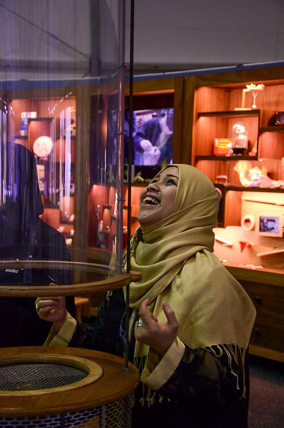 Enthusiasm for wind tubes is universal. Jehan Bantan, one of the Saudi facilitators trained by Exploratorium staff, enjoys the Wind Tube exhibit, Saudi Aramco Summer Cultural Program in Al Khobar, Saudi Arabia. Photo by Luigi Anzivino, Exploratorium