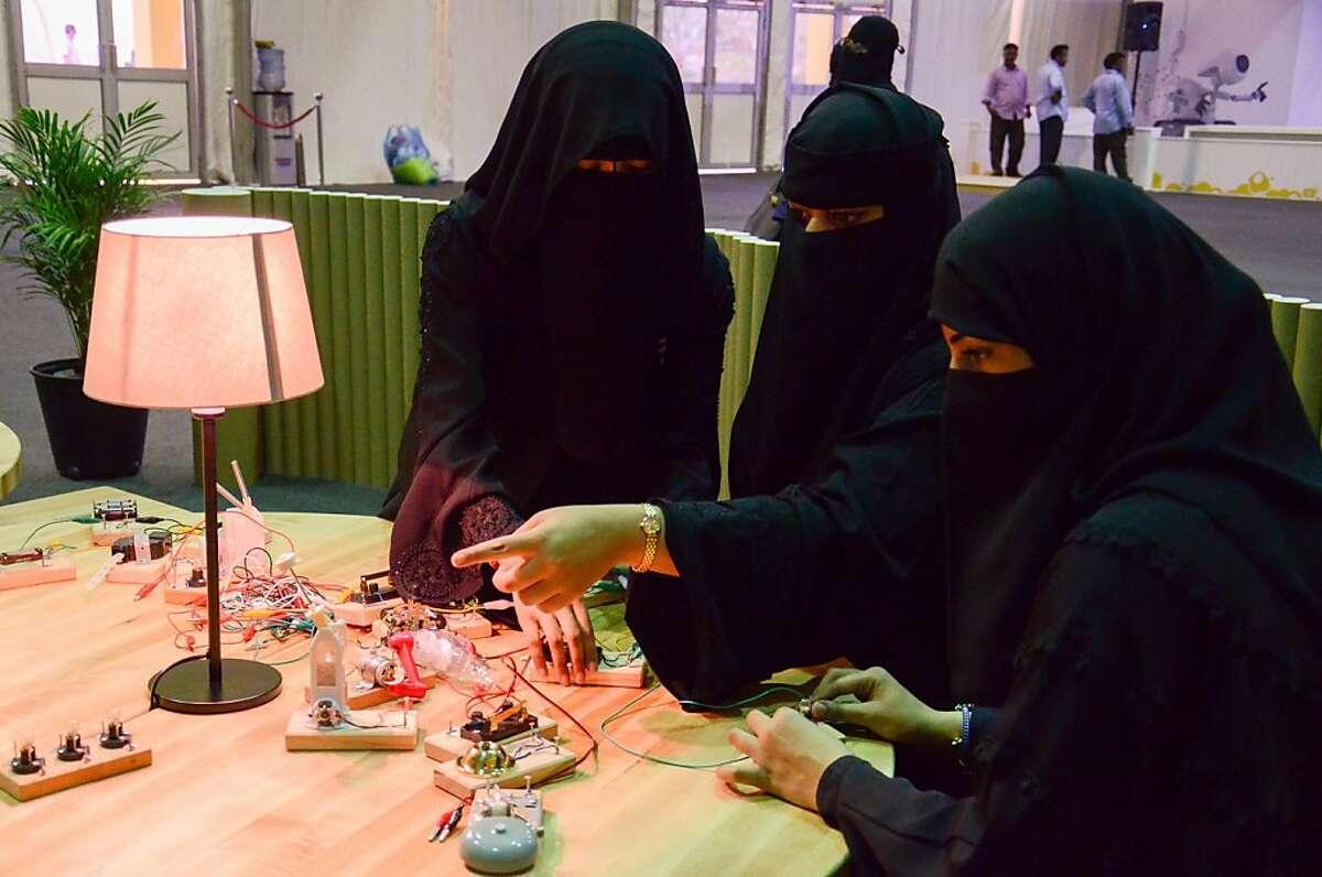 Three women collaborate in the Tinkering Studio, Saudi Aramco Summer Cultural Program in Al Khobar, Saudi Arabia. Photo by Luigi Anzivino, Exploratorium