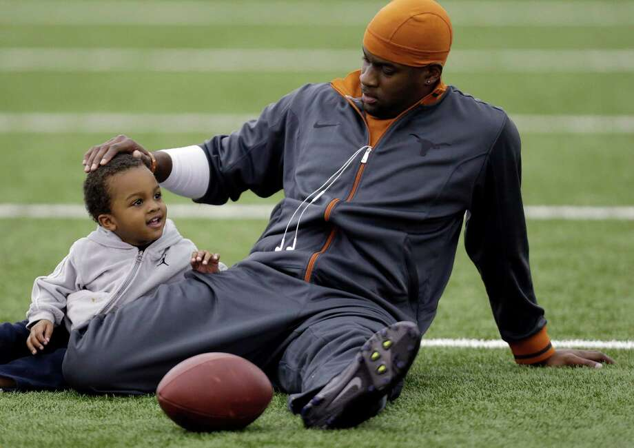 Former Texas and NFL quarterback Vince Young, right, stretches with his son, Jordan, 2, prior to throwing for scouts at Texas' Pro Day, Tuesday, March 26, 2013, in Austin, Texas. (AP Photo/Eric Gay) Photo: Eric Gay, Associated Press / AP