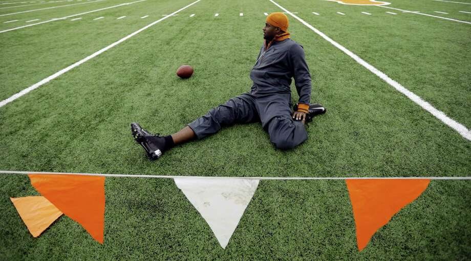 Texas alum and former NFL quarterback Vince Young stretches prior to throwing for scouts at Texas' NFL football pro day, Tuesday, March 26, 2013, in Austin, Texas. Young, who was cut by the Buffalo Bills in the 2012 preseason, is attempting a comeback. (AP Photo/Eric Gay) Photo: Eric Gay, Associated Press / AP