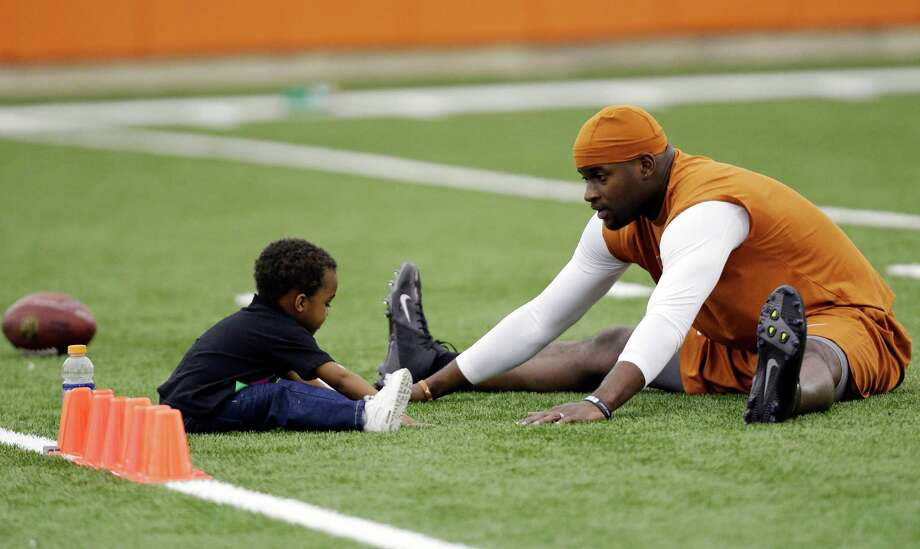 Texas alum and former NFL quarterback Vince Young right, stretches with his son, Jordan, 2, prior to throwing for scouts at Texas' NFL football pro day, Tuesday, March 26, 2013, in Austin, Texas. Young, who was cut by the Buffalo Bills in the 2012 preseason, is attempting a comeback. (AP Photo/Eric Gay) Photo: Eric Gay, Associated Press / AP
