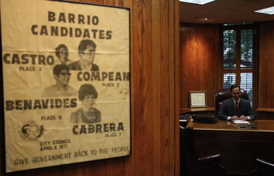 Julian Castro sits in his new office at City Hall. The poster, left, has a 1971 photo of his mother from her campaign with the Committee for Barrio Betterment. Photo: JOHN DAVENPORT, STAFF / jdavenport@express-news.net