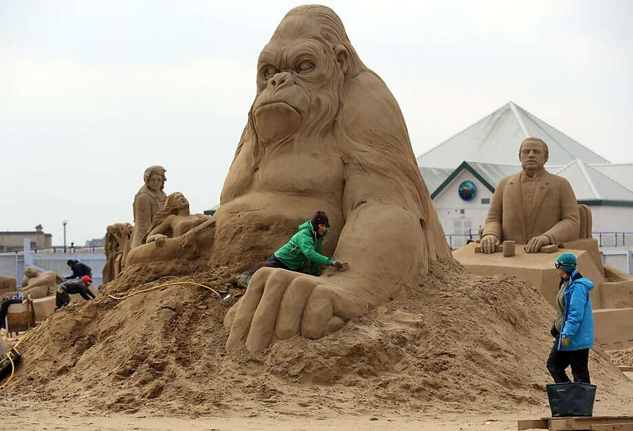 Dutch sand sculptor Helena Bangert patches up King Kong's arm, which he needs for climbing iconic landmarks. Photo: Matt Cardy, Getty Images