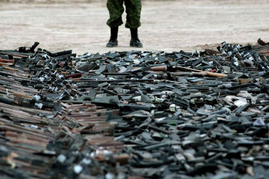 Thousands of guns lie on the ground before their destruction in Ciudad Juarez, Mexico on February 16, 2012. Photo: JESUS ALCAZAR, AFP/Getty Images / 2012 AFP