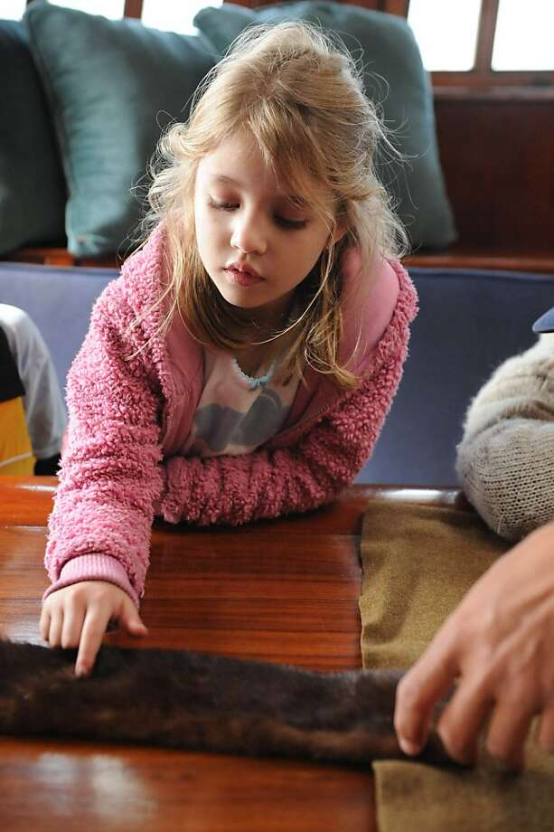 Erin Callaway feels mink fur on the Hawaiian Chieftain that is docked near the Bay Model Visitors Center in Sausalito on March 26, 2013. The crew is educating school children on trade history. The ship, along with the Lady Washington will be here until April 2, 2013. Photo: Susana Bates, Special To The Chronicle