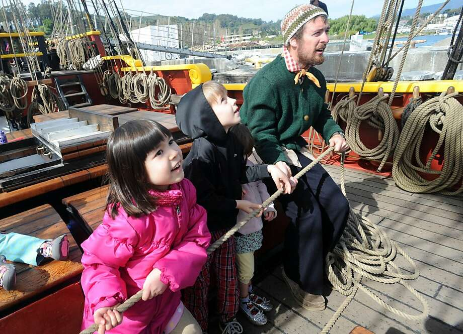 Caleb Stripes (right) help children including Kaylia Roark Hernandez (left) set a sail on the tall ship Lady Washington that is docked near the Bay Model Visitors Center in Sausalito on March 26, 2013. The ship, along with the Hawaiian Cheiftain, will be here until April 2, 2013. Photo: Susana Bates, Special To The Chronicle
