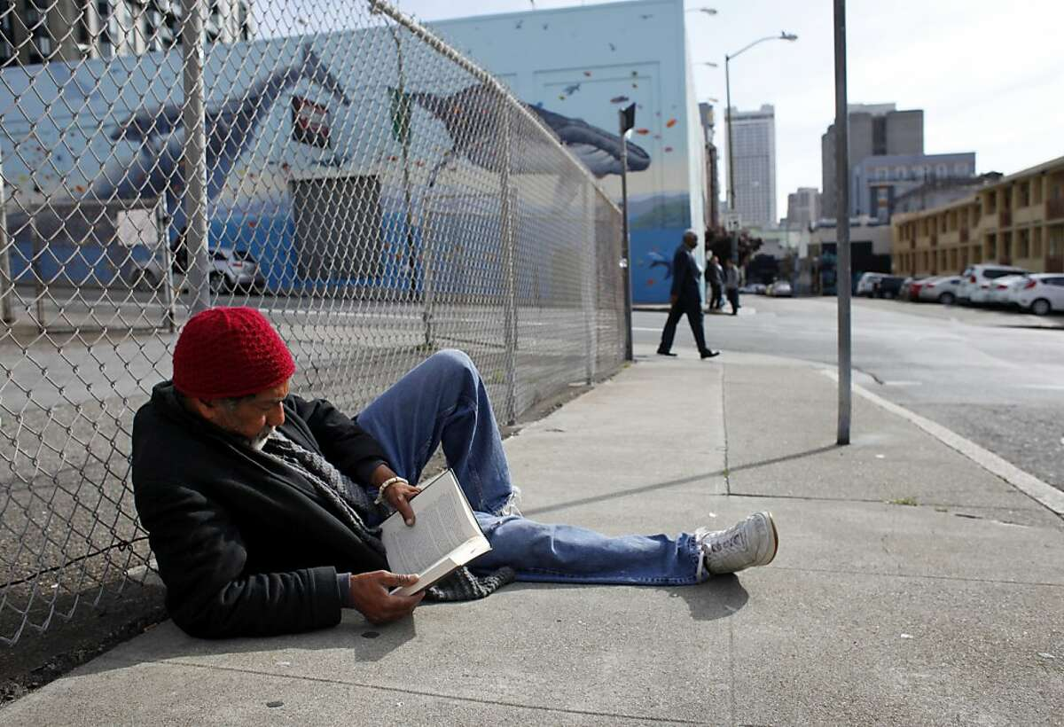 Jeffry Moore, 63, spends his morning reading John Lescroart's The Second Chair as he sits along Olive Street, Tuesday March 26, 2013, in San Francisco, Calif.