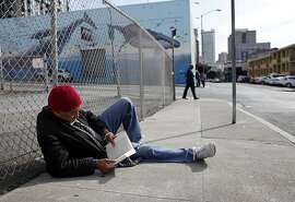 "Jeffry Moore, 63, spends his morning reading John Lescroart's The Second Chair as he sits along Olive Street,  Tuesday March 26, 2013, in San Francisco, Calif. "" I found this book and it gives me something to do with my time,"" says Moore."
