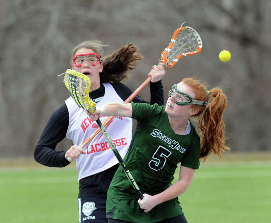 At left, Olivia Hompe of New Canaan in action against Ryan Taylor # 5 of Convent of the Sacred Heart during the girls high school lacrosse scrimmage between Convent of the Sacred Heart and New Canaan High School at Convent in Greenwich, Tuesday, March 26, 2013. Photo: Bob Luckey / Greenwich Time